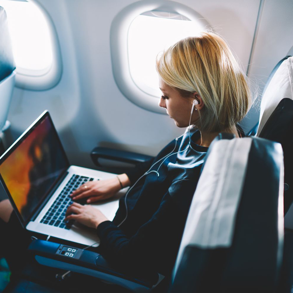 girl with laptop and headphones in the plane